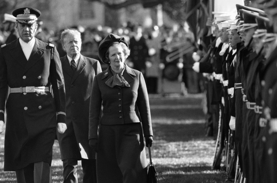 Photo - FILE - In this Dec. 17, 1979 file photo, British Prime Minister Margaret Thatcher  reviews the honor guard at the White House in Washington, as President Jimmy Carter follows.  At left in Col. Stanley Bonta, commander of the guard. Ex-spokesman Tim Bell says that Thatcher has died. She was 87. Bell said the woman known to friends and foes as