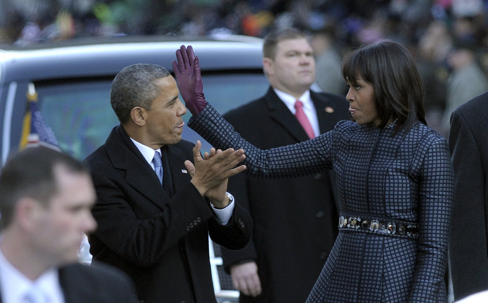 Photo - President Barack Obama and first lady Michelle Obama walk in the Inaugural Parade after the ceremonial swearing-in for the 57th Presidential Inauguration on Capitol Hill in Washington, Monday, Jan. 21, 2013. (AP Photo/Susan Walsh) ORG XMIT: DCSW105