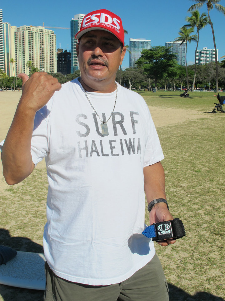 Photo - Wilson Vinano, holds a shark deterrent device he invented, the Electronic Shark Defense System, in Honolulu on Dec. 17, 2013. A surge in shark attacks on Maui hasn't stopped people from surfing and swimming in the warm ocean waters that surround this Hawaiian island. But it has spurred sales of devices that claim to keep sharks away by emitting an electric pulse. (AP Photo/Audrey McAvoy)