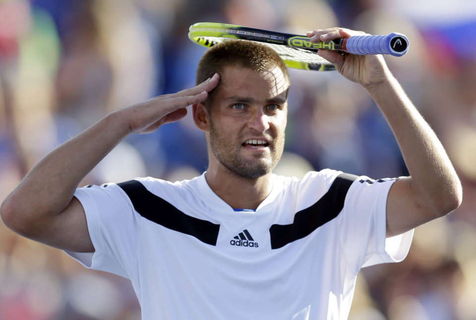 Mikhail Youzhny, of Russia, salutes the crowd after beating Lleyton Hewitt, of Australia, during the fourth round of the 2013 U.S. Open tennis tournament, Tuesday, Sept. 3, 2013, in New York. (AP Photo/Kathy Willens)