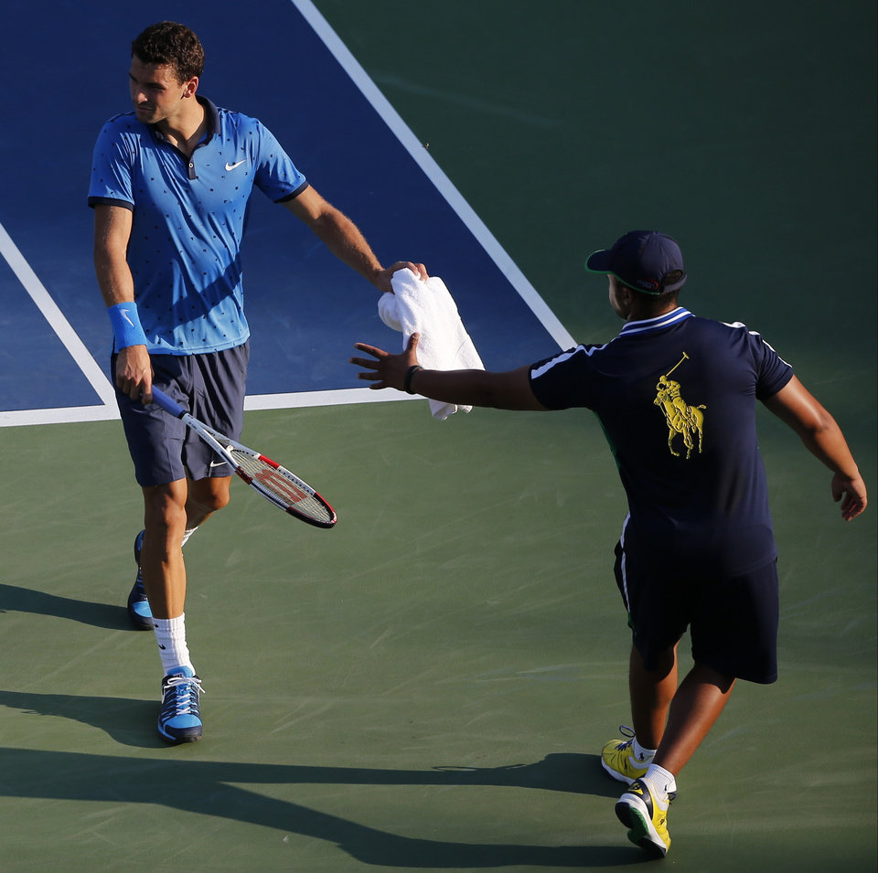 Photo - Grigor Dimitrov, of Bulgaria, hands a towel back to a ball person after wiping sweat from his face during the second round of the 2014 U.S. Open tennis tournament, Wednesday, Aug. 27, 2014, in New York. (AP Photo/Elise Amendola)
