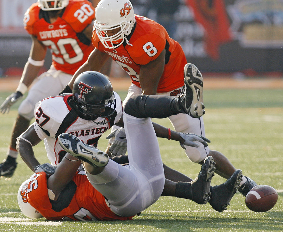 Photo - Texas Tech's Edward Britton (27) fumbles the ball after getting hit by Oklahoma State's Kellen Tillman (56) during the second half of the college football game between the Oklahoma State University Cowboys (OSU) and the Texas Tech University Red Raiders (TTU) at Boone Pickens Stadium in Stilllwater, Okla., on Saturday, Sept. 22, 2007. OSU won, 49-45. By NATE BILLINGS, The Oklahoman