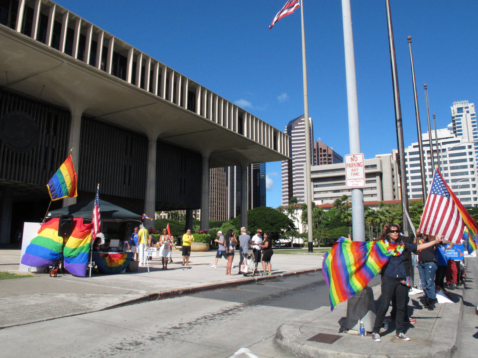 Photo - Gay marriage supporters rally outside the Hawaii Capitol in Honolulu ahead of a Senate vote on whether to legalize same-sex marriage on Tuesday, Nov. 12, 2013. The bill allowing same-sex couples to wed on the islands starting Dec. 2 is expected to pass easily barring any unexpected surprises. (AP Photo/Oskar Garcia)