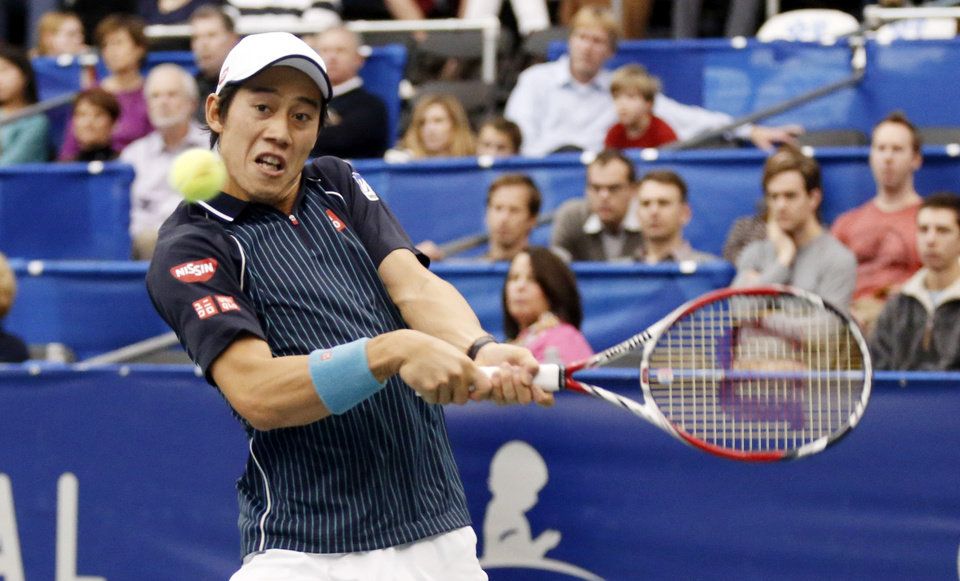 Photo - Kei Nishikori, of Japan, hits a return to Ivo Karlovic, of Croatia, in the singles final at the U.S. National Indoor Tennis Championships on Sunday, Feb. 16, 2014, in Memphis, Tenn. (AP Photo/Rogelio V. Solis)