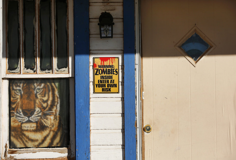 "Photo -  Signs on either side of the front door of the house reference zombies. One says: ""Certified zombie killer."" Another reads: ""Warning: zombies inside enter at your own risk.""    Jim Beckel -  THE OKLAHOMAN"
