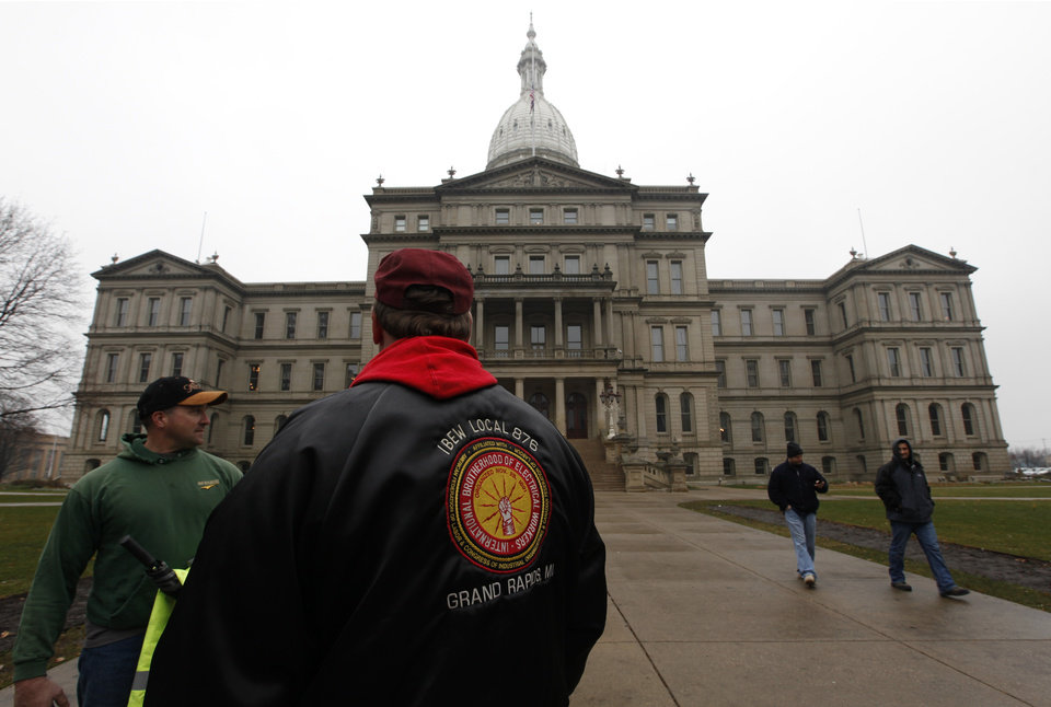 International Brotherhood of Electrical Workers members stand outside the capitol in Lansing, Friday, Dec. 7, 2012. Michigan could become the 24th state with a right-to-work law next week. Rules require a five-day wait before the House and Senate vote on each other's bills; lawmakers are scheduled to reconvene Tuesday and Gov.Snyder has pledged to sign the bills into law. (AP Photo/Paul Sancya)
