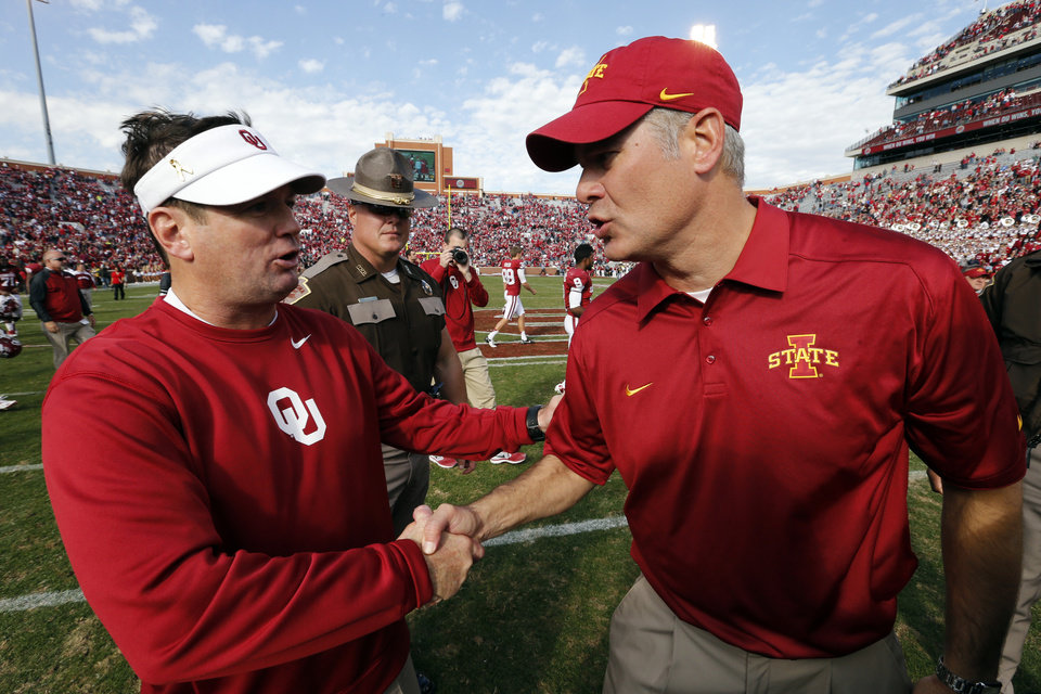 Photo - Oklahoma head coach Bob Stoops greets Iowa State head coach Paul Rhoads at midfield following the college football game between the University of Oklahoma Sooners (OU) and the Iowa State University Cyclones (ISU) at Gaylord Family-Oklahoma Memorial Stadium in Norman, Okla. on Saturday, Nov. 16, 2013. Photo by Steve Sisney, The Oklahoman