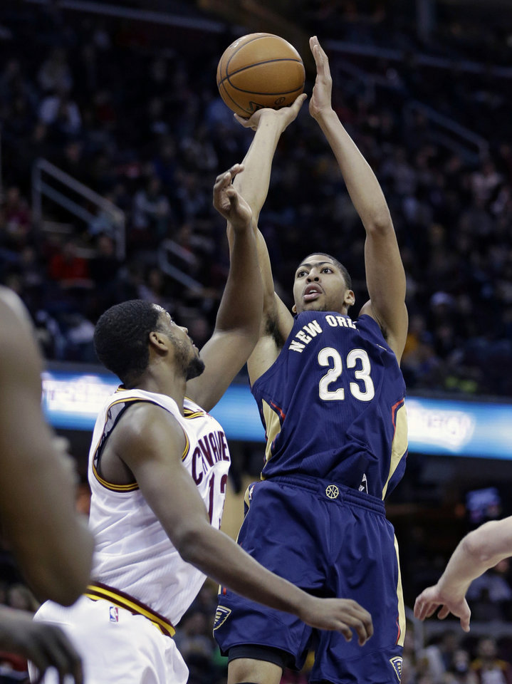 Photo - New Orleans Pelicans' Anthony Davis (23) shoots over Cleveland Cavaliers' Tristan Thompson (13), of Canada, during the first quarter of an NBA basketball game, Tuesday, Jan. 28, 2014, in Cleveland. (AP Photo/Tony Dejak)