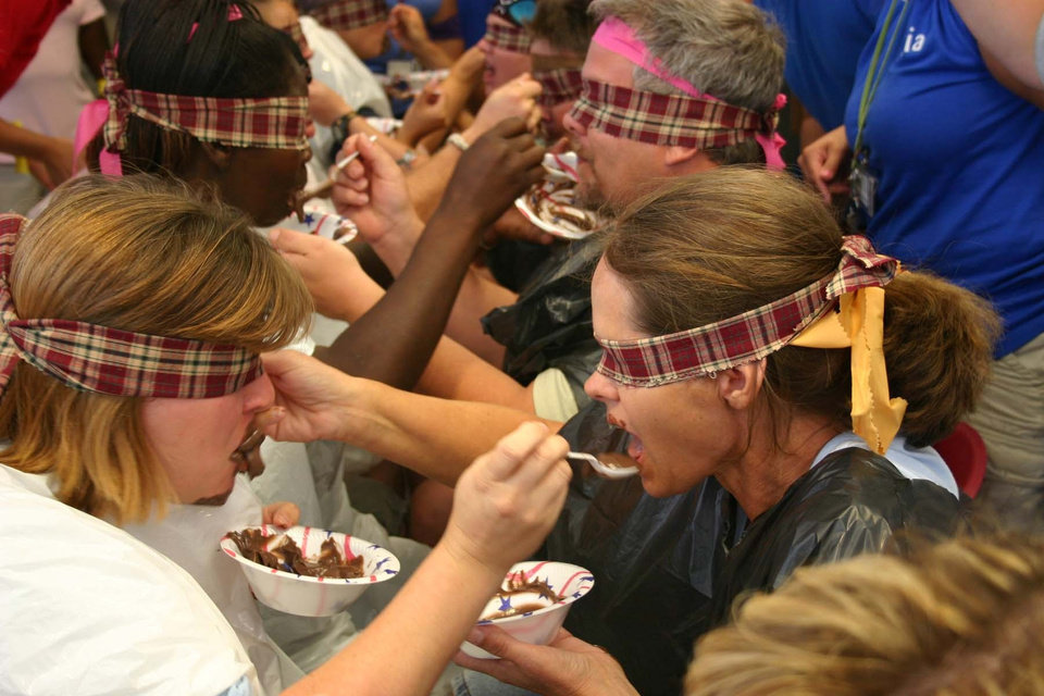 Spoon feeding. One of the tasks to be completed during the J. D. McCarty Center's Amazing Race team building exercise was for two team members to feed each other a bowl of chocolate pudding while blindfolded. Only the team member's knees could be touching for this event. The Amazing Race was the kickoff event for the McCarty Center's month long employee appreciation month.<br/><b>Community Photo By:</b> Greg Gaston<br/><b>Submitted By:</b> Greg,
