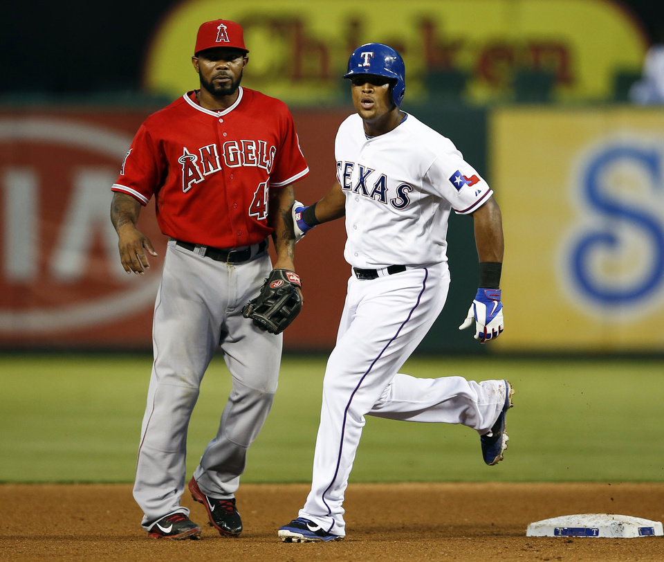 Photo - Texas Rangers' Adrian Beltre, right, pats Los Angeles Angels second baseman Howie Kendrick on the arm as he steals second on a wild pitch thrown by Angles's pitcher Garrett Richards during the fourth inning of a baseball game, Friday, Aug. 15, 2014, in Arlington, Texas. (AP Photo/Jim Cowsert)