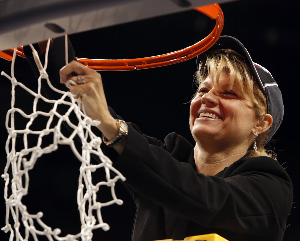 Photo - Sooner head coach Sherri Coale finishes cutting down the net after her team's 74-68 win as the University of Oklahoma (OU) defeats Purdue in the NCAA women's basketball regional tournament finals at the Ford Center in Oklahoma City, Okla., on Tuesday, March 31, 2009.  Photo by Steve Sisney, The Oklahoman