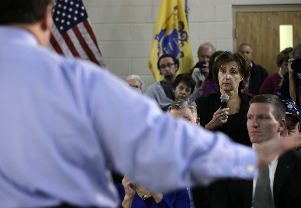Photo - New Jersey Gov. Chris Christie answers a question from Marion Romano, second right, during a town hall meeting at Saint Mary's of The Pines Church Parish Wednesday, Jan. 16, 2013, in Manahawkin, N.J. Romano asked why she was told it might take years for the federal government to make final decisions on Advisory Base Flood Elevatiopns after Superstorm Sandy. Christie said that it was he who would make the decisions and it was only going to take him weeks, not years. (AP Photo/Mel Evans)
