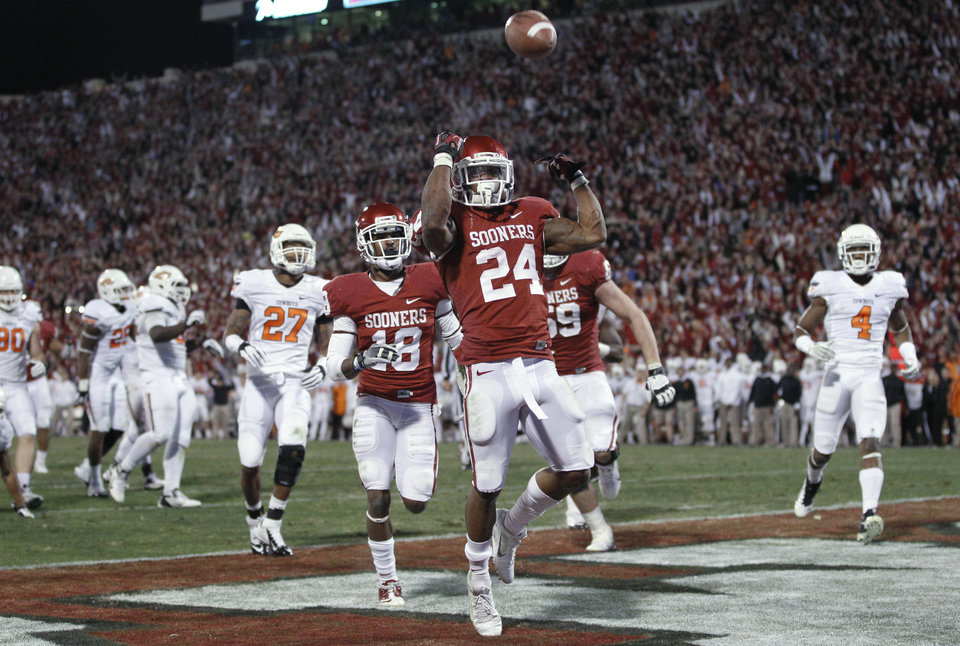 Oklahoma running back Brennan Clay (24) celebrates after scoring the game winning touchdown against Oklahoma State in overtime of an NCAA college football game in Norman, Okla., Saturday, Nov. 24, 2012. Oklahoma won in overtime 51-48. (AP Photo/Sue Ogrocki)