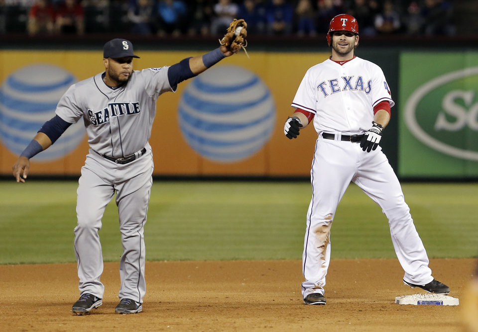 Photo - Texas Rangers' Mitch Moreland, right, reacts after being tagged out by Seattle Mariners second baseman Robinson Cano, left, during the fourth inning of a baseball game on Wednesday, April 16, 2014, in Arlington, Texas. (AP Photo/Brandon Wade)