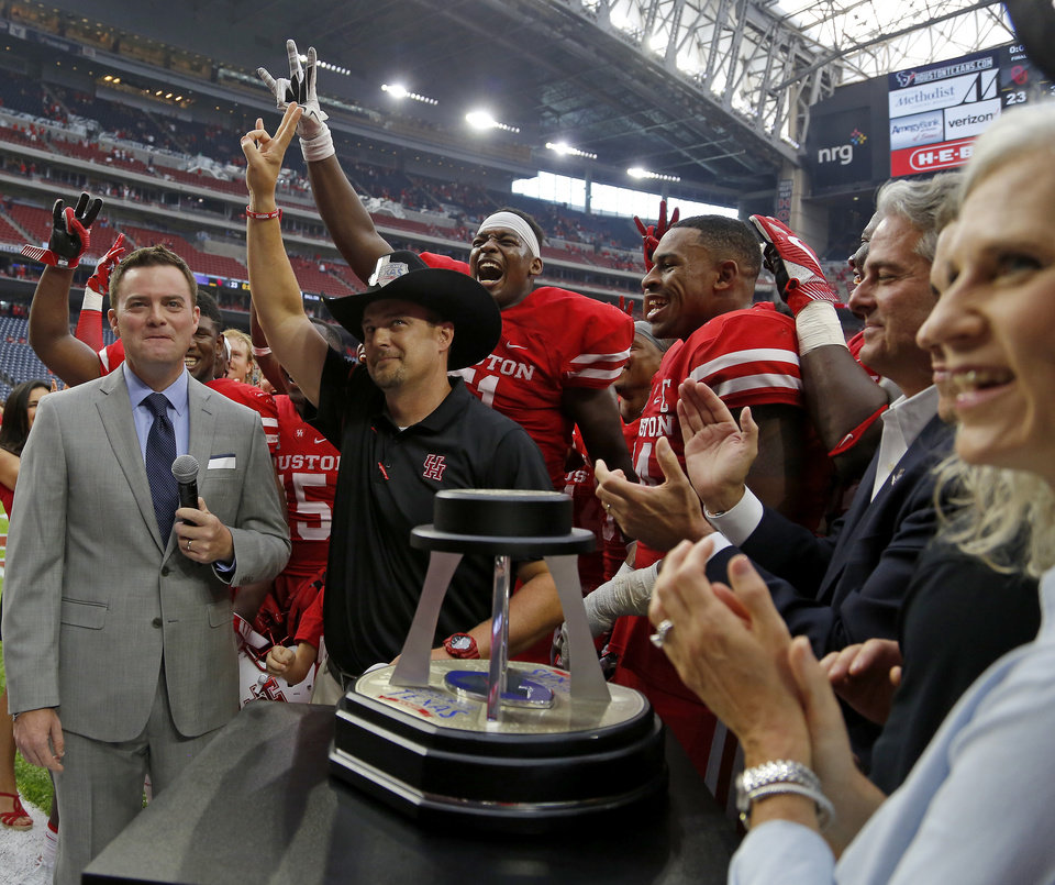 Photo - Houston coach Tom Herman celebrates with his team after the AdvoCare Texas Kickoff college football game between the University of Oklahoma Sooners (OU) and the Houston Cougars at NRG Stadium in Houston, Saturday, Sept. 3, 2016. Houston won 33-23. Photo by Bryan Terry, The Oklahoman