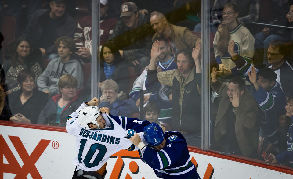 Fans watch as San Jose Sharks\' Andrew Desjardins, left, and Vancouver Canucks\' Kevin Bieksa fight during third period NHL hockey action in Vancouver, British Columbia, on Thursday Nov. 14, 2013. (AP Photo/The Canadian Press, Darryl Dyck)