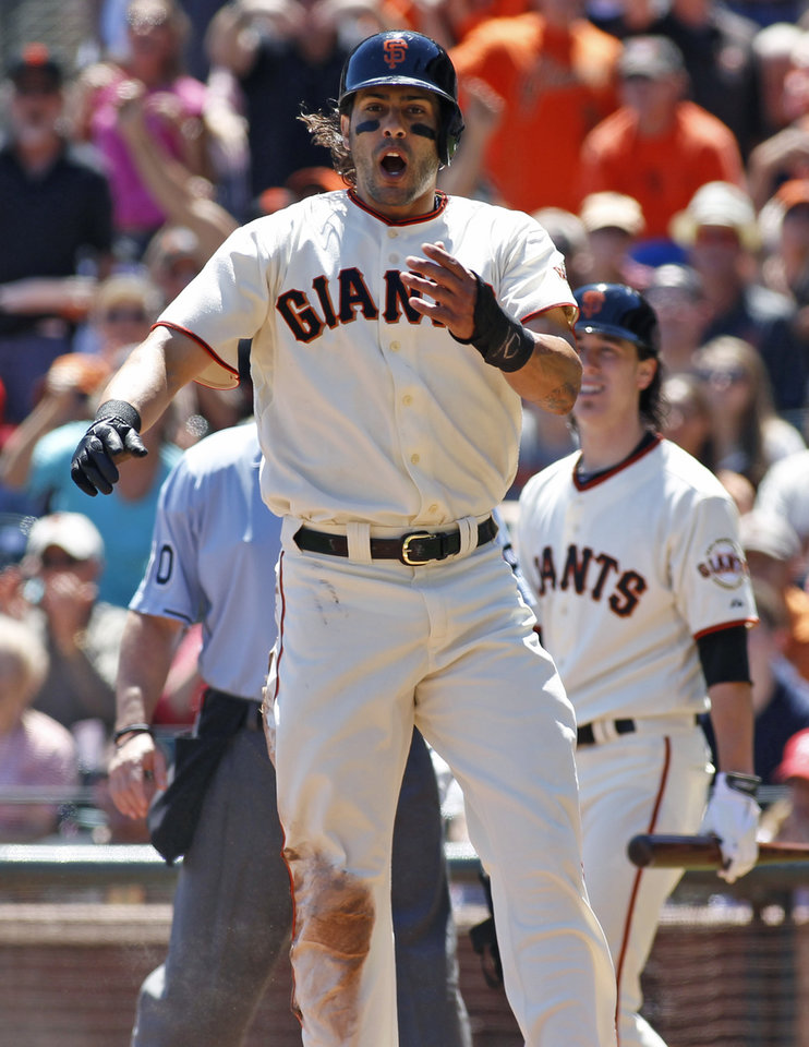 Photo - San Francisco Giants'  Michael Morse reacts after scoring against the Philadelphia Phillies during the second inning of a baseball game, Sunday, Aug. 17, 2014 in San Francisco. Giants pitcher Tim Lincecum is in the background. (AP Photo/George Nikitin)