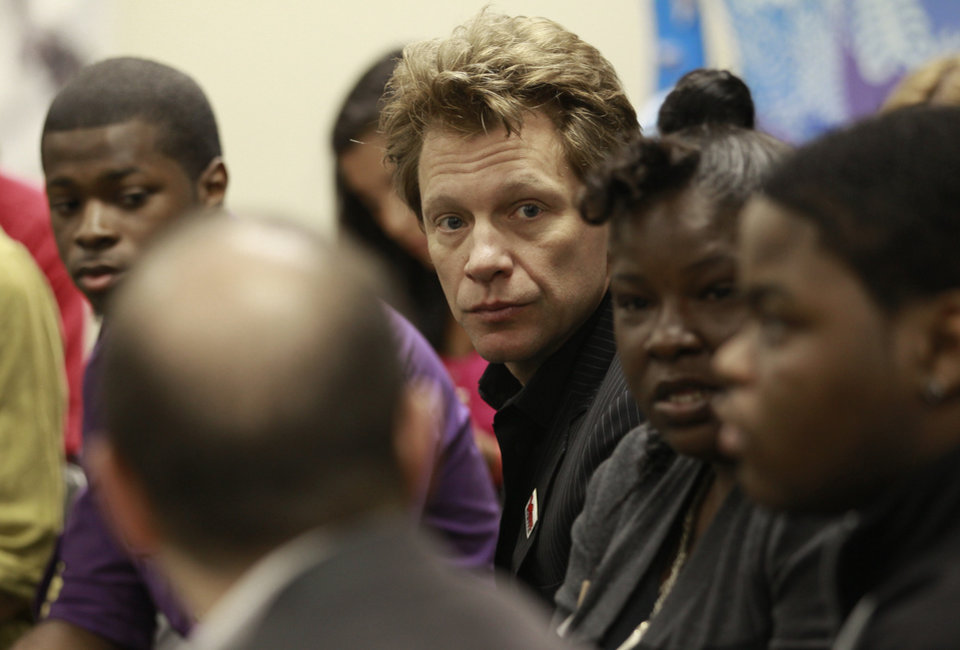 Photo -   Musician Jon Bon Jovi, center, listens as people talk during a visit to Youth Education & Employment Success Center, Monday, June 6, 2011 in Newark, N.J. Bon Jovi, a member of the White House Council for Community Solutions and chairman of the Jon Bon Jovi Soul Foundation, made the visit to close out a four-city tour talking to teens about education. (AP Photo/Julio Cortez)