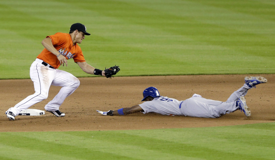 Photo - Miami Marlins second baseman Derek Dietrich, left, prepares to tag out Los Angeles Dodgers' Dee Gordon who was attempting to steal second in the fifth inning of a baseball game on Sunday, May 4, 2014, in Miami. (AP Photo/Wilfredo Lee)