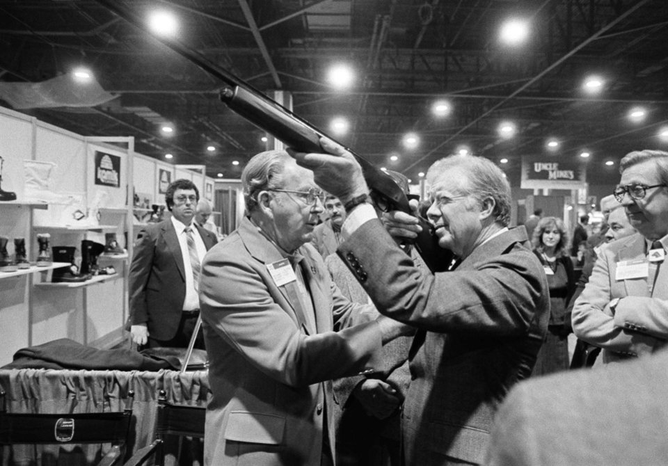 FILE - In this Nov. 14, 1984 file photo, former President Jimmy Carter sights down the barrel of a shotgun as Reinhart Fajen, a gunstock manufacturer, checks the fit, in Atlanta as Carter stopped during a visit to the national shooting sports foundation shot show at the World Congress Center. The White House has released a photo of President Barack Obama firing a gun, two days before he is set to travel to Minnesota to discuss gun control. It shows Obama shooting at clay targets on the range at Camp David, the presidential retreat in Maryland, where he says he engages in the sport