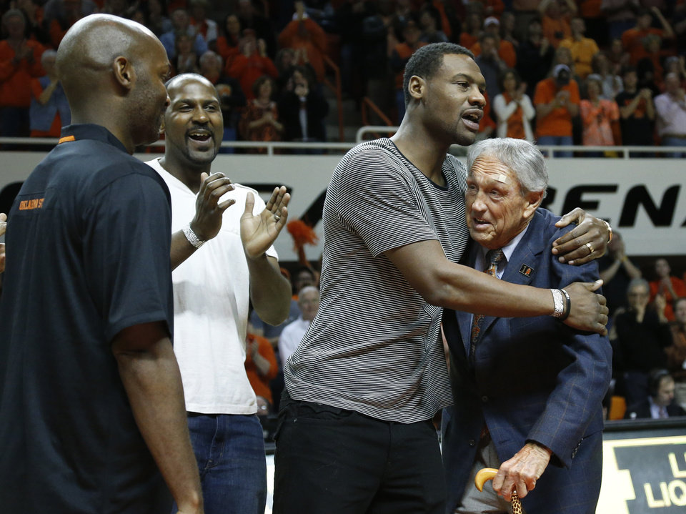 Photo - Former Oklahoma State basketball player Tony Allen, second from right, hugs former head coach Eddie Sutton, right, during ceremonies in honor of the 2004 OSU team which reached the Final Four, during halftime of an NCAA college basketball game between Oklahoma and Oklahoma State in Stillwater, Okla., Saturday, Feb. 15, 2014. Looking on at left are John Lucas III and Ivan McFarlin. (AP Photo/Sue Ogrocki)