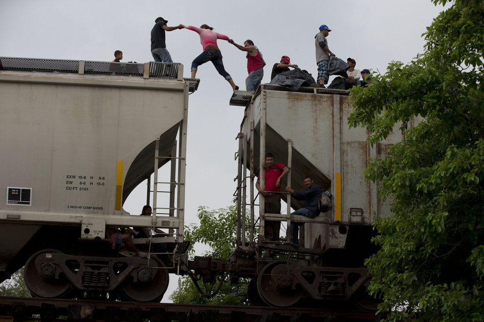 Photo - In this June 20, 2014 photo, a woman is helped from one boxcar to another, as Central American migrants wait atop the train they were riding north, hours after it suffered a minor  derailment in a remote wooded area outside Reforma de Pineda, Chiapas state, Mexico. Many migrants who say they are fleeing criminal violence generally are not eligible for political asylum, which is reserved for groups persecuted for their beliefs or identities. U.N. officials say there is no way of forcing the U.S. and Mexico to accept Central Americans as refugees, but a broad-based change in terminology could bring pressure on the two countries to do more. (AP Photo/Rebecca Blackwell)