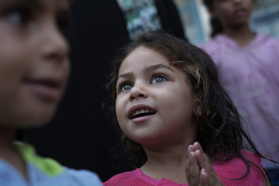 Photo - Displaced Palestinian girl Rahaf Al Attar, 3, participates in a play session with other children, at a U.N. school where they had sought refuge along with their families during the war, in Gaza City, Gaza Strip, Thursday, Aug. 7, 2014. Rahaf had been staying at the school with her family, originally from Beit Lahiya, in the norther Gaza Strip for 20 days. Taking advantage of the continuing ceasefire, volunteers from the local non-profit NGO 'Tomooh' (Ambition), arranged a special play session for children to try and lessen the stress they've been enduring after the weeks of conflict. In the playground the children got a chance to sing and play group games under the caring eye of volunteers. They hope that their efforts will lessen the damage of the traumatic recent weeks events, or at least help them forget for a short while. (AP Photo/Lefteris Pitarakis)