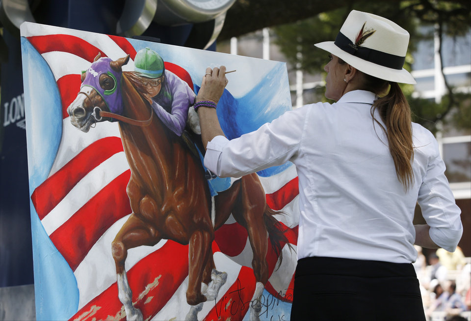 Photo - Artist Susan Sommer-Luarca, of Springfield, Mo., paints an image of Triple Crown hopeful California Chrome outside the grandstand at Belmont Park during the undercard races for the Belmont Stakes horse race, Saturday, June 7, 2014, in Elmont, N.Y. (AP Photo/Kathy Willens)