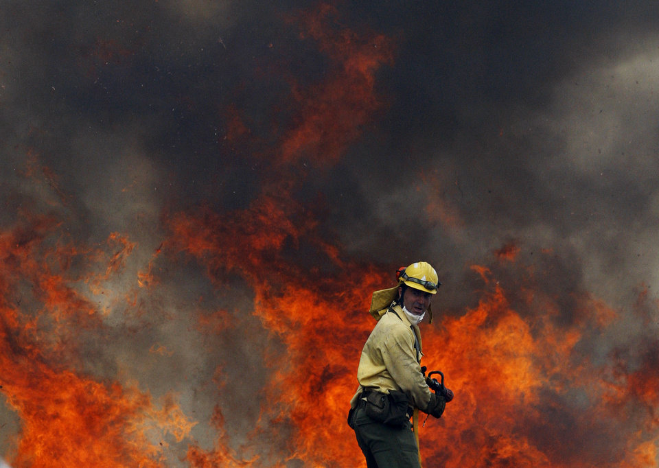 Photo -   A firefighter tries to control a raging forest fire in Ojen, southern Spain, Friday, Aug. 31, 2012. Spanish officials say some 4,000 people have been evacuated from their houses as a wildfire abetted by strong winds spread rapidly through hills around the popular southern tourist city of Marbella. (AP Photo/Sergio Torres)