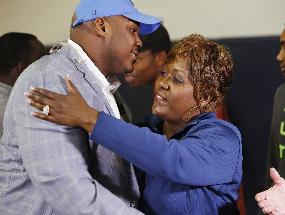 Photo - Casady High School football athlete Josh Wariboko-Alali gets a hug from his mother Lisa during signing day ceremonies at Casady High School in Oklahoma City Wednesday, Feb. 4, 2015. Photo by Paul B. Southerland, The Oklahoman