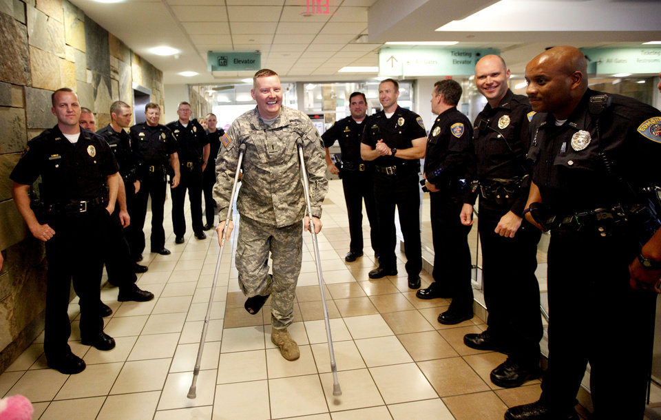 Edmond Police officer Kyle Stoy and Oklahoma National Guard soldier is greeted by fellow officers as he arrives at Will Rogers World Airport in  Oklahoma City, Thursday, March 22, 2012. Photo by Sarah Phipps, The Oklahoman.