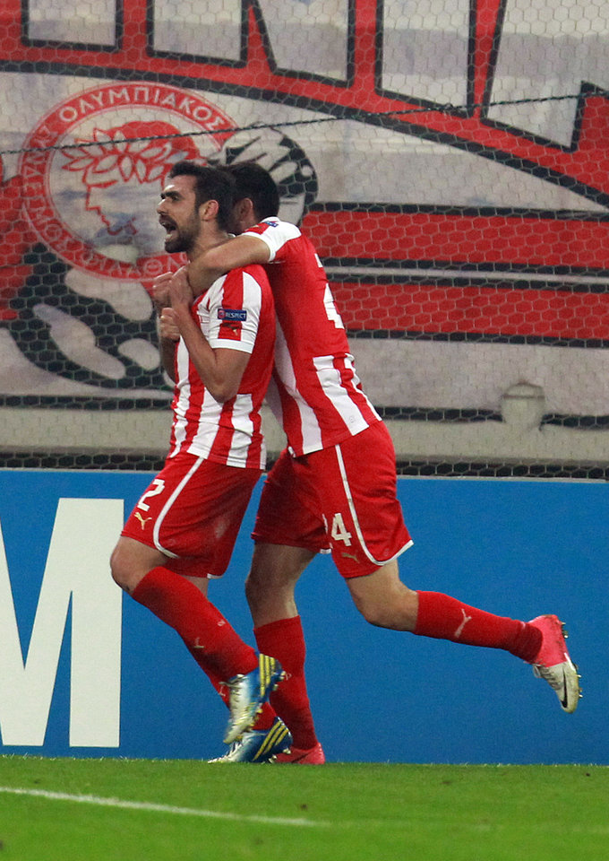 Photo - Olympiakos' Giannis Maniatis celebrates with teammate Kostas Manolas after scoring against Arsenal during a group B Champions League soccer match in the port of Piraeus, near Athens, Tuesday, Dec. 4, 2012. (AP Photo/Thanassis Stavrakis)