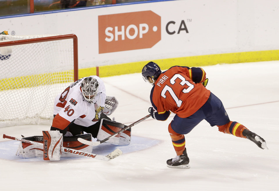 Photo - Florida Panthers center Brandon Pirri (73) scores against Ottawa Senators goalie Robin Lehner (40) during a shootout in an NHL hockey game, Tuesday, March 25, 2014 in Sunrise, Fla. The Panthers defeated the Senators 3-2. (AP Photo/Wilfredo Lee)