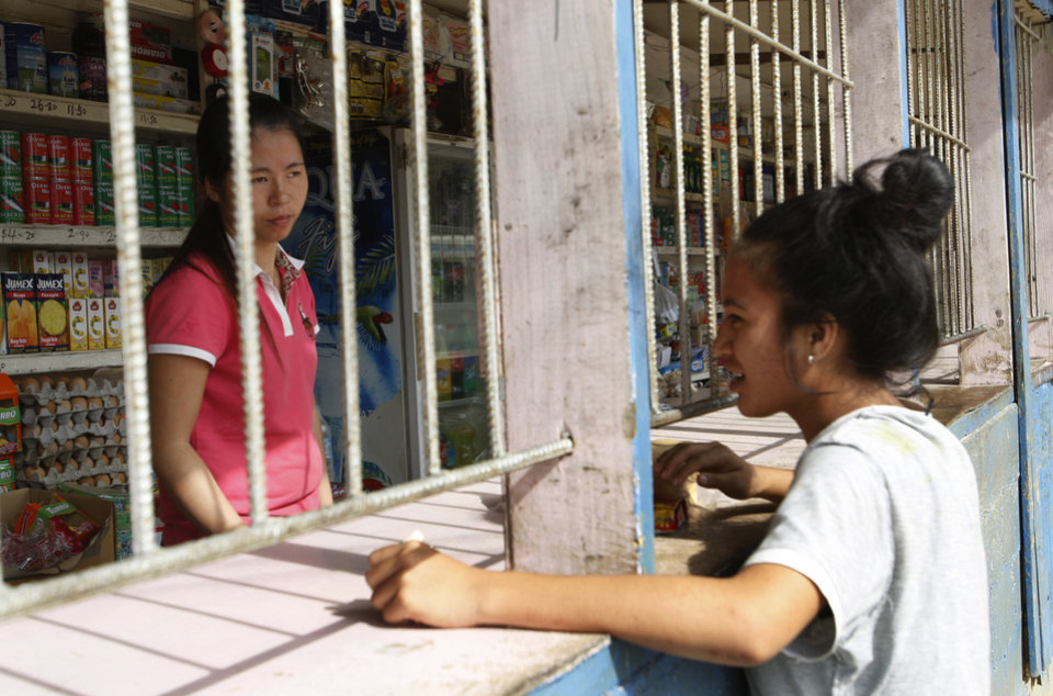Photo - In this Wednesday, June 4, 2014 photo, a customer buys bread and other goods at a roadside store in Vaini, near Nuku'alofa, Tonga. Many of the stores, including this one, are operated by Chinese immigrants and protected with bars. New Zealand tourists attracted by the country's beauty have been staying away due to a dispute over the safety of the plane. The dispute represents a small skirmish in a broader battle for global influence. (AP Photo/Nick Perry)