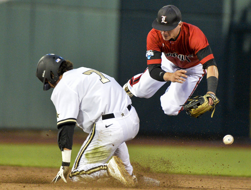 Photo - Vanderbilt's Dansby Swanson (7) steals second base against Louisville shortstop Sutton Whiting, right, and advances to third base on a throwing error in the fourth inning of an NCAA baseball College World Series game in Omaha, Neb., Saturday, June 14, 2014. (AP Photo/Ted Kirk)