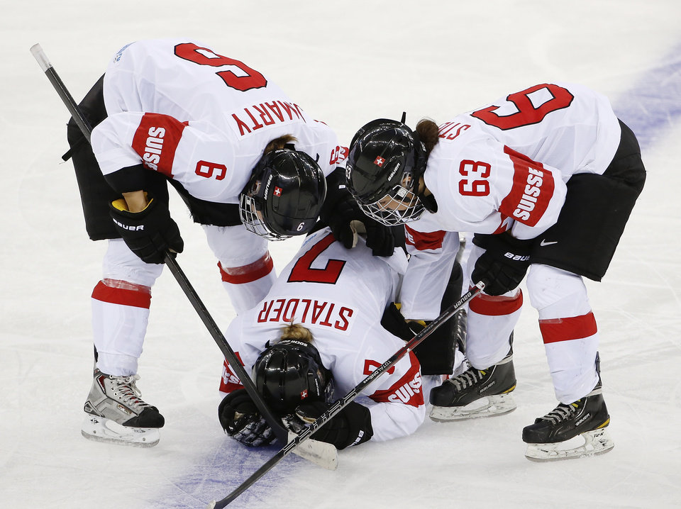Photo - Julia Marty (6) and Anja Stiefel of Switzerland (63) check on their injured teammate Lara Stalder during the third period of the game against USA at the 2014 Winter Olympics women's ice hockey match at Shayba Arena, Monday, Feb. 10, 2014, in Sochi, Russia. (AP Photo/Petr David Josek)