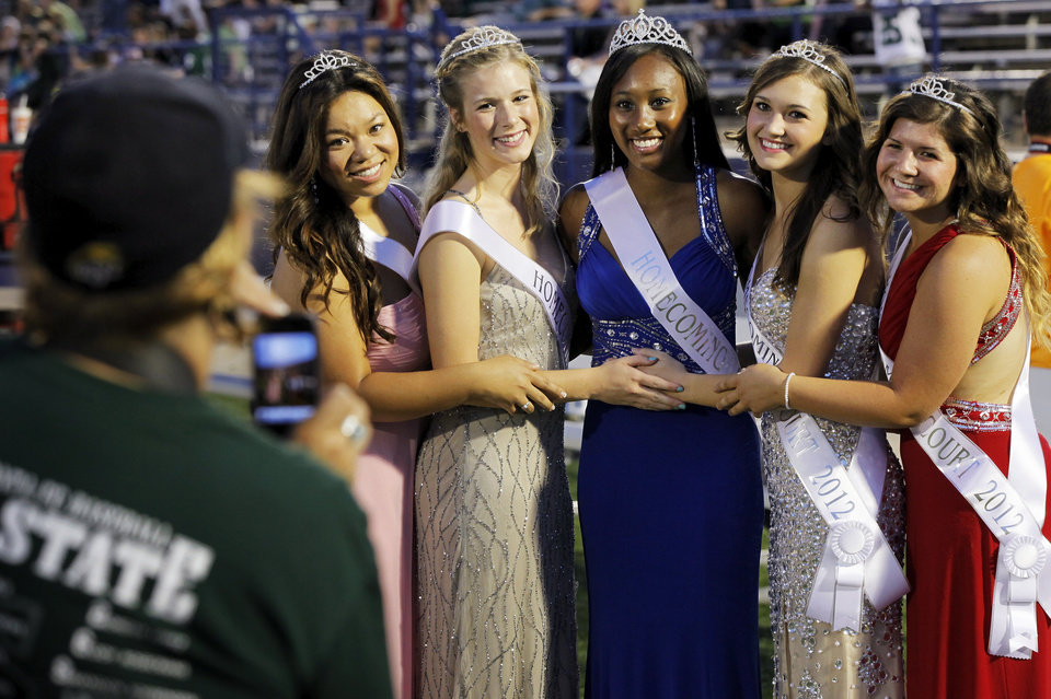 Photo - The members of the Edmond Santa Fe Homecoming Court, from left, Jenney Huynh, Meghan Hook, Cameerah Graves, Megan Turner and Danielle Taylor, pose as Anne Schmidt, left, takes a photo during a high school football game between Edmond Santa Fe and Southmoore at Wantland Stadium in Edmond, Okla., Thursday, Sept. 20, 2012. Photo by Nate Billings, The Oklahoman