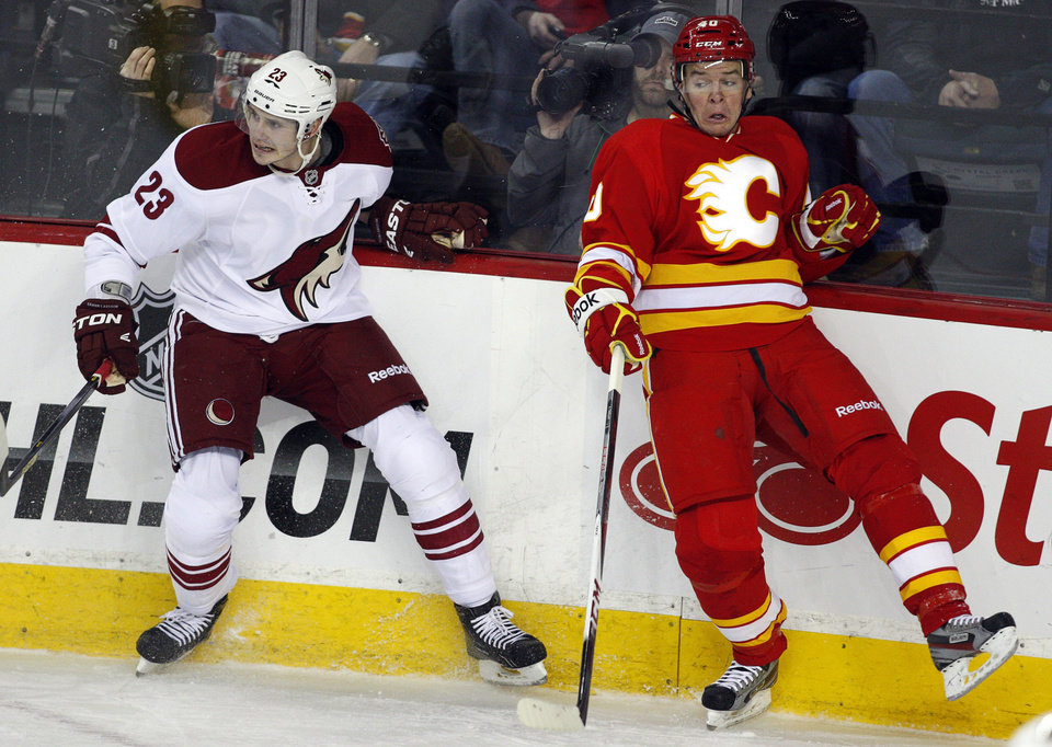 Phoenix Coyotes' Oliver Ekman-Larsson, left, from Sweden, dodges a check by Calgary Flames' Matt Stajan during the first period of an NHL hockey game in Calgary, Alberta, Sunday, Feb. 24, 2013. (AP Photo/The Canadian Press, Jeff McIntosh)