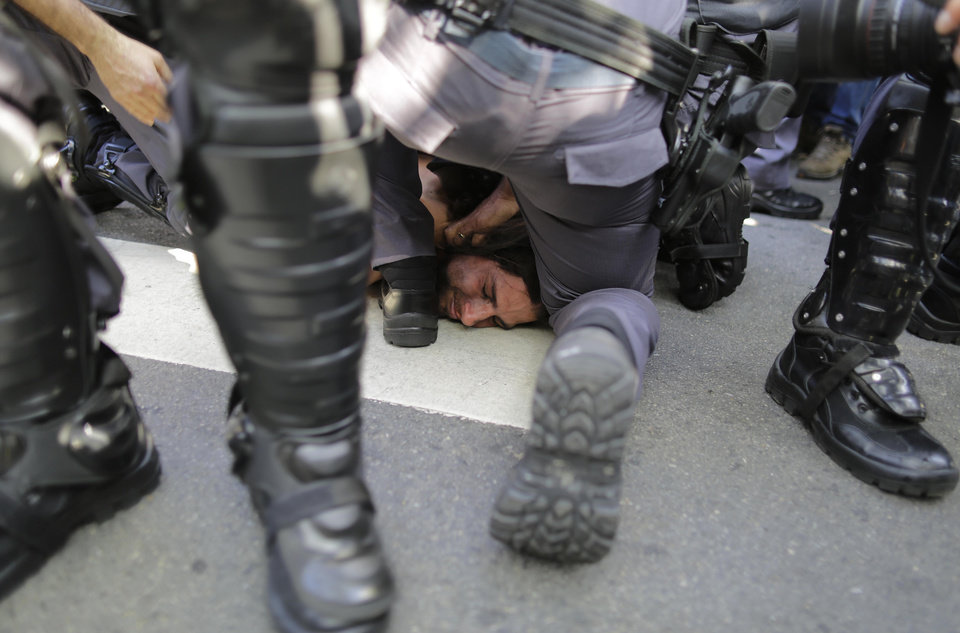 Photo - A protester is detained by police during a demonstration demanding better public services and protesting the money spent on the World Cup soccer tournament in Sao Paulo, Brazil, Thursday, June 12, 2014. Brazilian police clashed with anti-World Cup protesters trying to block part of the main highway leading to the stadium that hosts the opening match of the tournament. (AP Photo/Nelson Antoine)