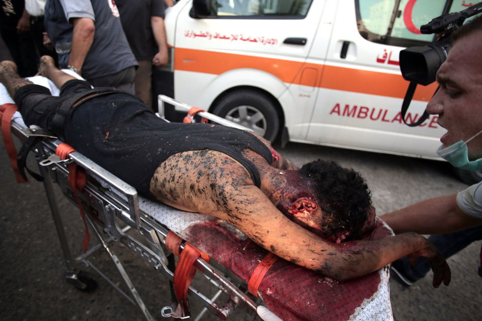 Photo - Palestinian medics wheel a wounded man, following an Israeli Strike in Shijaiyah neighborhood, to the emergency room of the Shifa Hospital, in Gaza City, Wednesday, July 30, 2014. (AP Photo/Khalil Hamra)