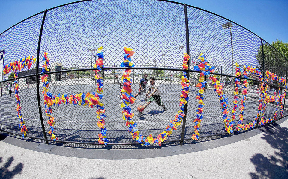 Photo - Players shoot some hoops Monday at the Downtown Community Basketball Court. The fence is decorated in support of the Oklahoma City Thunder. Photo by Chris Landsberger, The Oklahoman