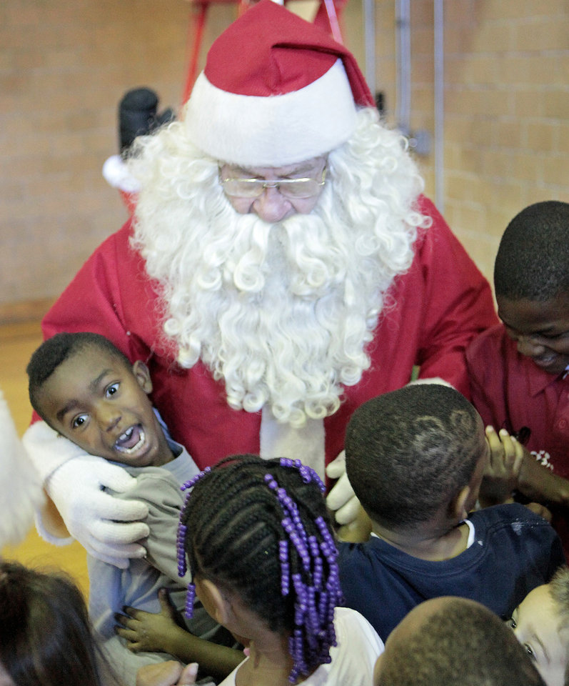 Joshua Powell, 7, left, and other children at the City Rescue Mission hug Santa, J.D. Simpson, Friday, December 23 , 2011.  Santa Claus is J.D. Simpson and he has been playing Santa at the  City Rescue Mission since 1984.Photo by David McDaniel, The Oklahoman