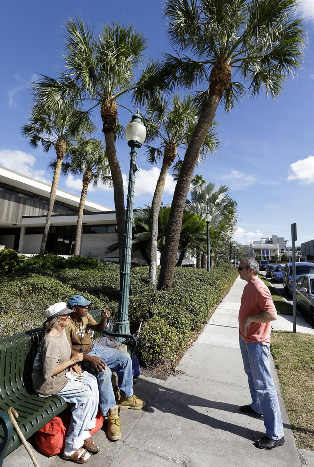 In a Friday, Jan. 11, 2013 photo, legal Consultant Michael Barfield, right, talk to Cindy Edlund, left, and James Franklin Jr., both of which are homeless, as they sit on a park bench outside the Sarasota City Hall Friday, Jan. 11, 2013, in Sarasota, Fla. Newer, wealthy residents in the Gulf Coast city known for its arts scene and beautiful beaches are buying expensive downtown condos so they can live an urban lifestyle _ but don't want the problems associated with a city, including the 700 or so homeless people who inhabit the county, the American Civil Liberties Union and others contend.(AP Photo/Chris O'Meara)