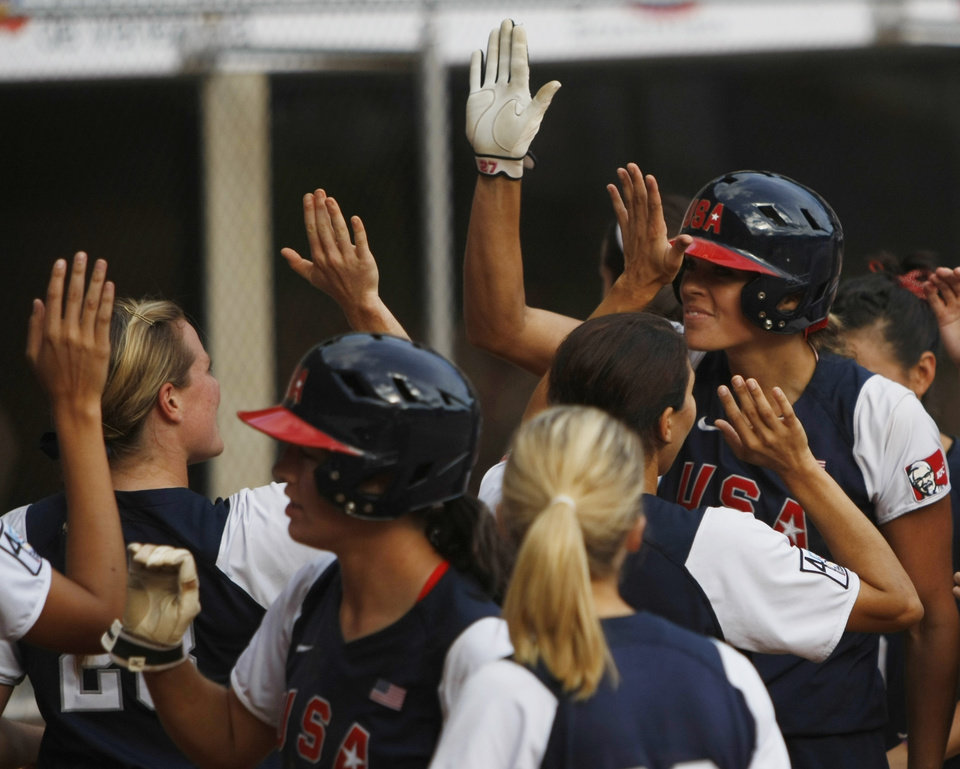 U.S. player Jennie Finch, right, is congratulated by her teammates after she hit a home run, scoring three points against Canada, during a Women\'s Softball World Championship game in Caracas, Wednesday, June 30, 2010. U.S. won 16-1. (AP Photo/Fernando Llano)