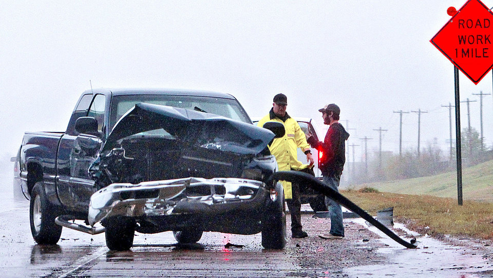 Photo - An Oklahoma Highway Patrol trooper works the scene of an accident Monday on Interstate 40 in Oklahoma City. Rain caused problems for some motorists.