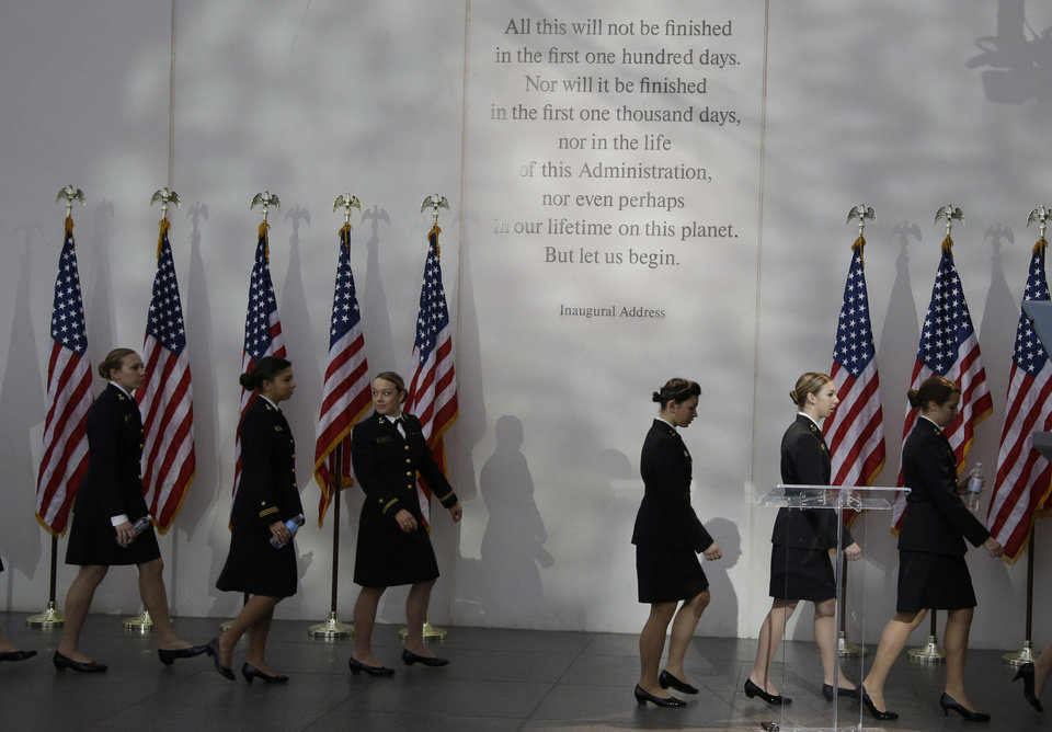 Photo - Members of the U.S. Naval Academy Women's Glee Club walk under a passage from President John F. Kennedy's inaugural address before a ceremony to commemorate the 50th anniversary of Kennedy's assassination at the John F. Kennedy Library and Museum in Boston. Kennedy, the 35th President of the United States, was assassinated in Dallas 50 years ago today. (AP Photo/Stephan Savoia)