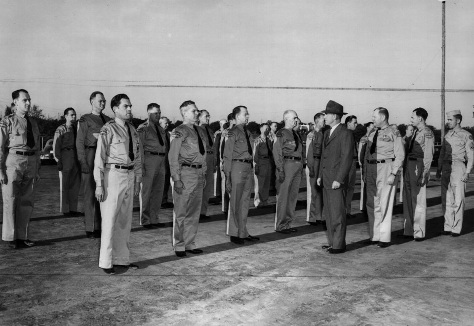 Photo - L.D. Callahan, vice-chairman of the county-city civilian defense council, inspects the Oklahoma City unit of the state highway patrol auxiliary in 1942. The patrol used a civilian auxiliary during World War II after more than two thirds of its troopers enlisted or were drafted for military service.  STAFF PHOTOGRAPHER - STAFF PHOTOGRAPHER