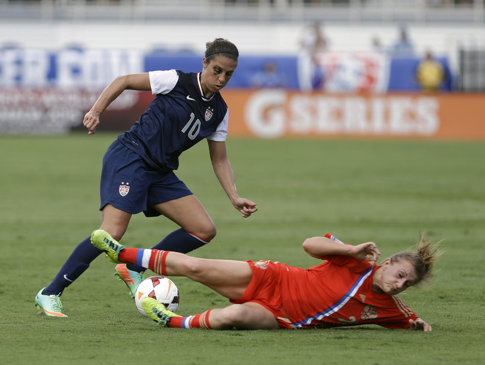 Photo - Russia's Nelli Korovkina, right, tries to steal the ball from United State's Carli Lloyd (10) during an international friendly soccer match in Boca Raton, Fla., Saturday, Feb. 8, 2014. The U.S. won 7-0. (AP Photo/Alan Diaz)