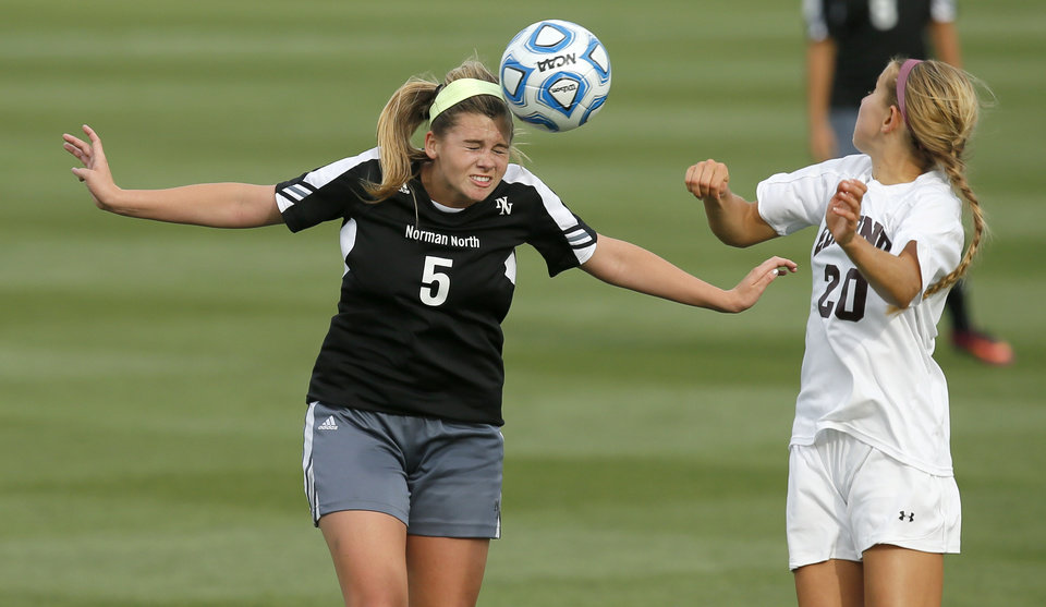 Photo - Norman North's Camille Greer, left, heads the ball beside Edmond Memorial's Lana Duke during the Class 6A girls soccer championship between Edmond Memorial and Norman North in Norman, Okla., Friday, May 16, 2014. Photo by Bryan Terry, The Oklahoman