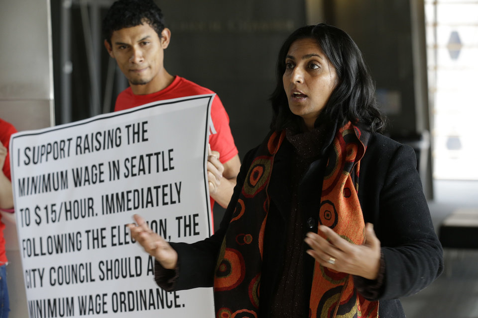 In this photo taken Nov. 4, 2013, Socialist candidate for Seattle City Council Kshama Sawant, right, speaks outside City Council chambers in Seattle about her support for raising the minimum wage to $15 an hour for all workers in the city. Sawant is challenging four-term Councilman Richard Conlin. (AP Photo/Ted S. Warren)